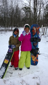 The kids grabbing their snowboards to enjoy the snowy downhill ride in the backyard of our Poconos home .